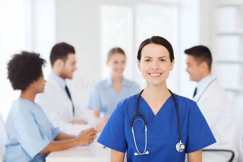 Ευτυχής γιατρός πέρα από την ομάδα γιατρών στο νοσοκομείο στοκ εικόνα με δικαίωμα ελεύθερης χρήσης