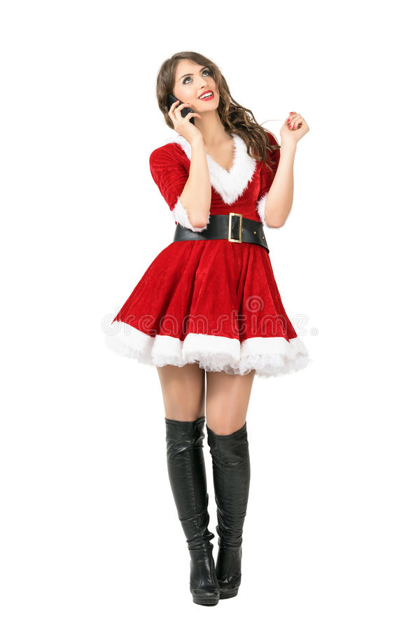 Ευτυχής γυναίκα Άγιου Βασίλη Χριστουγέννων που μιλά στο κινητό τηλέφωνο που ανατρέχει στοκ φωτογραφία με δικαίωμα ελεύθερης χρήσης