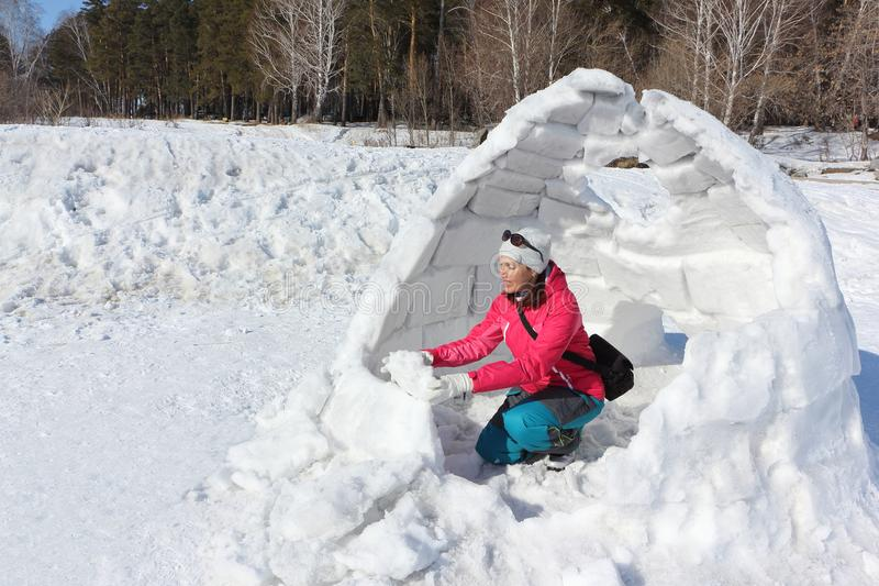 Ευτυχής γυναίκα ένα κόκκινο σακάκι που χτίζει μια παγοκαλύβα στοκ εικόνες με δικαίωμα ελεύθερης χρήσης