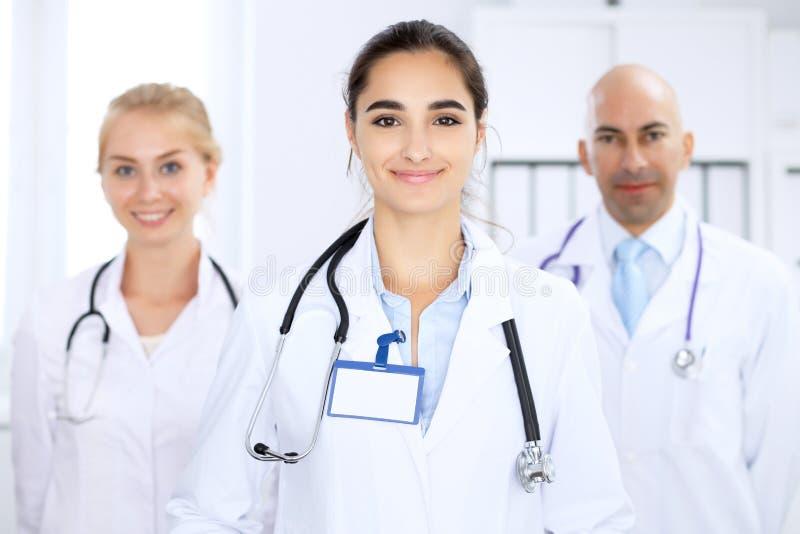 Ευτυχής γυναίκα γιατρών με το ιατρικό προσωπικό στο νοσοκομείο στοκ φωτογραφία με δικαίωμα ελεύθερης χρήσης