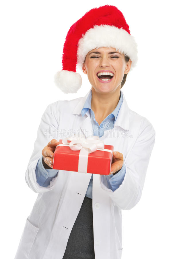 Ευτυχής γυναίκα γιατρών στο καπέλο santa που δίνει το κιβώτιο χριστουγεννιάτικου δώρου στοκ φωτογραφία με δικαίωμα ελεύθερης χρήσης