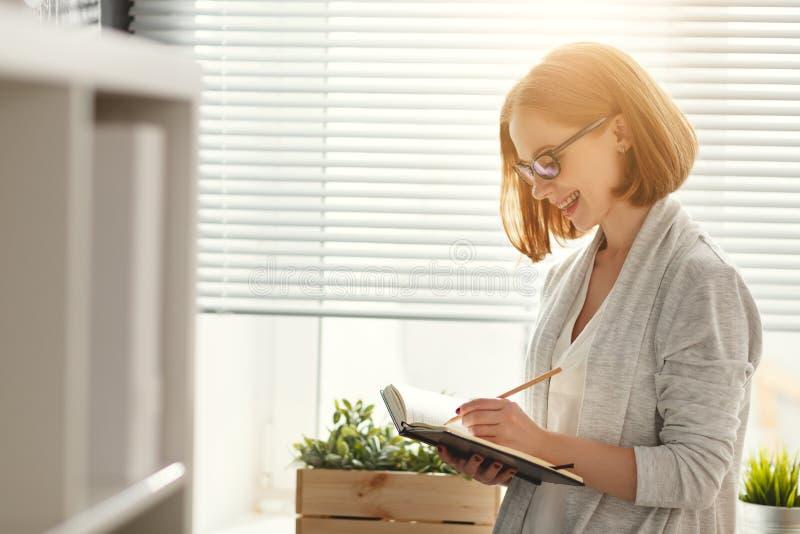 Ευτυχής γυναίκα επιχειρηματιών στο σχολικό πίνακα με τον προγραμματισμό προγράμματος στοκ εικόνα