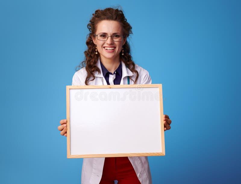 Ευτυχής γυναίκα ιατρών που παρουσιάζει κενό πίνακα στο μπλε στοκ εικόνα