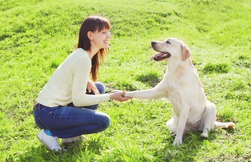 Ευτυχής γυναίκα ιδιοκτητών με retriever του Λαμπραντόρ τα τραίνα σκυλιών στοκ εικόνες