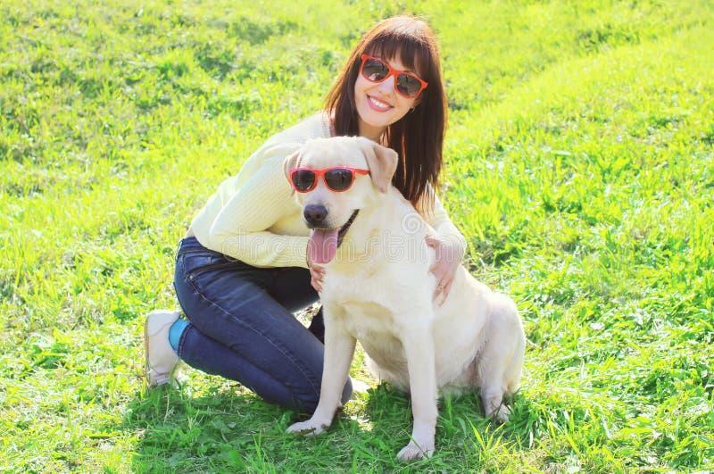 Ευτυχής γυναίκα ιδιοκτητών με retriever του Λαμπραντόρ το σκυλί στα γυαλιά ηλίου στοκ εικόνες