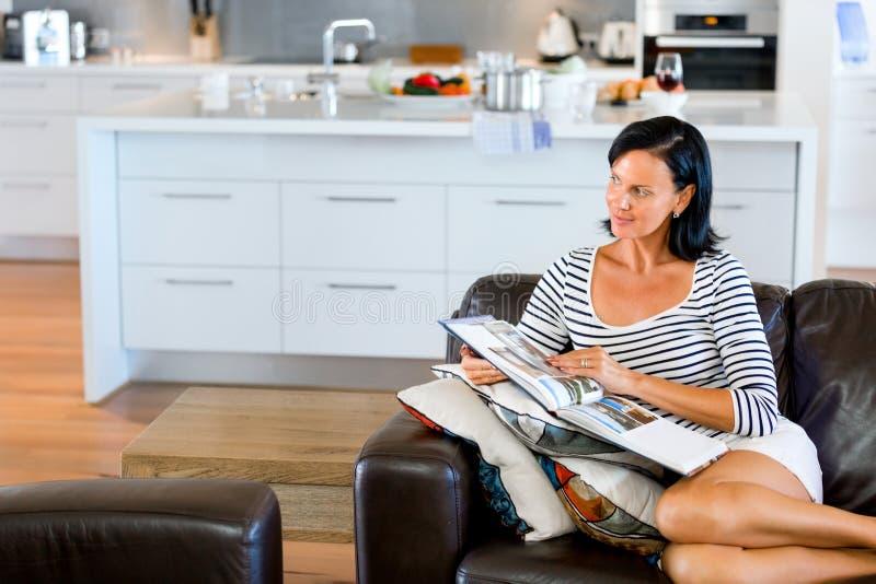 ευτυχής γυναίκα καναπέδ&om στοκ εικόνες