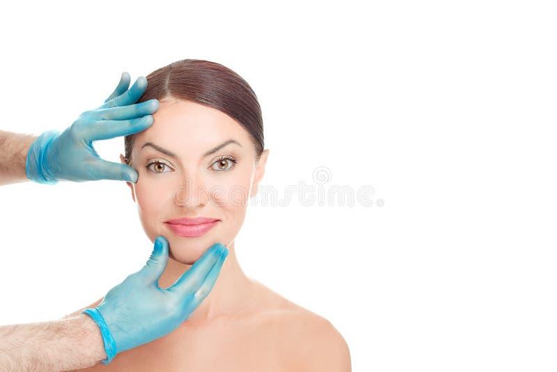 Ευτυχής γυναίκα μετά από την αισθητική χειρουργική επέμβαση, χαμόγελα ενώ ο γιατρός παρουσιάζει τα αποτελέσματα Άσπρη ανασκόπηση στοκ φωτογραφία με δικαίωμα ελεύθερης χρήσης