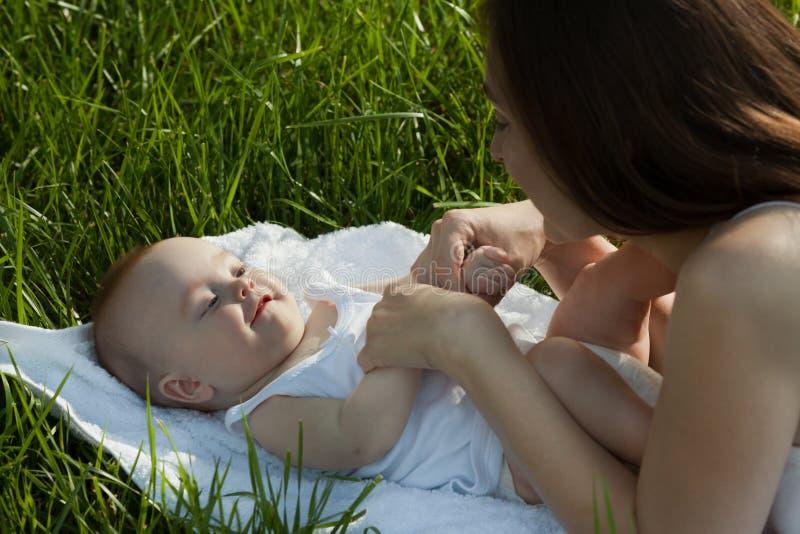 Ευτυχής γυναίκα με λατρευτό να βρεθεί μωρών στη χλόη οικογένεια ευτυχής στοκ φωτογραφία με δικαίωμα ελεύθερης χρήσης