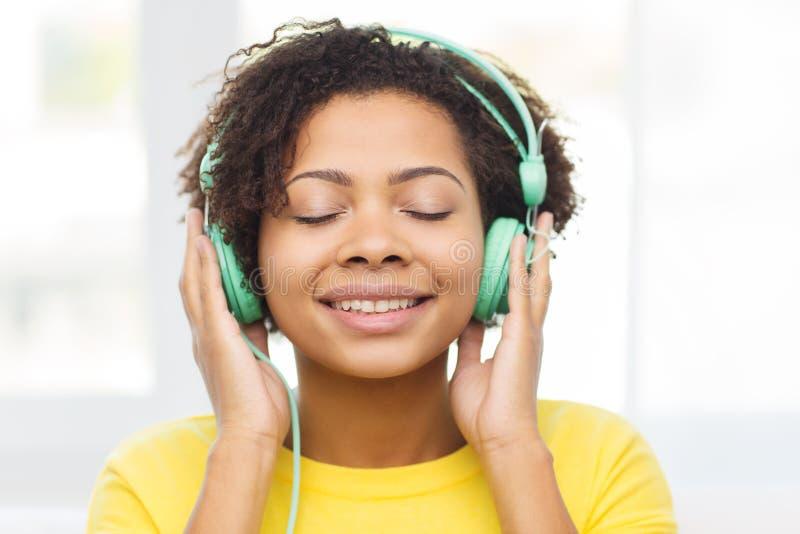 Ευτυχής γυναίκα με τα ακουστικά που ακούει τη μουσική στοκ εικόνες με δικαίωμα ελεύθερης χρήσης