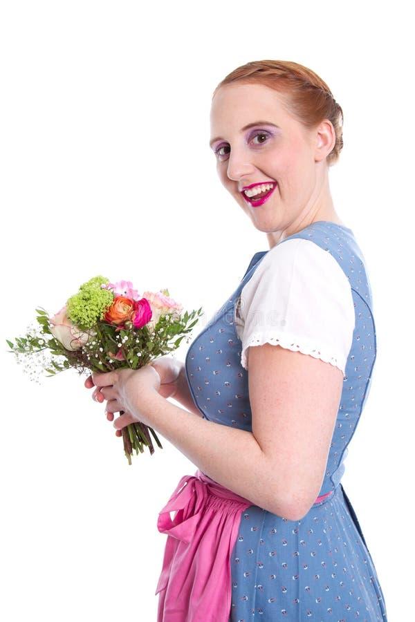 Ευτυχής γυναίκα με τα λουλούδια - που απομονώνονται - στο φόρεμα dirndl στοκ εικόνα με δικαίωμα ελεύθερης χρήσης