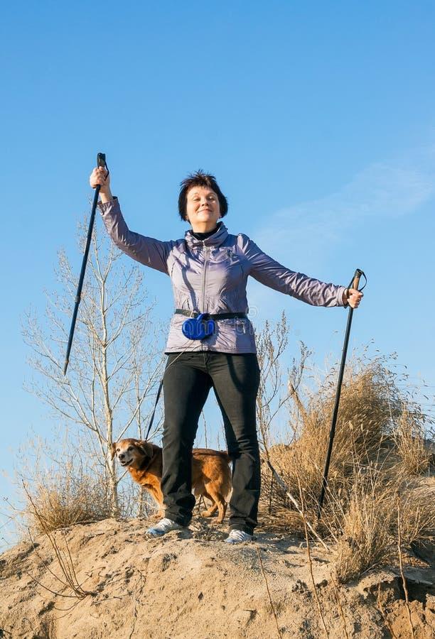 Ευτυχής γυναίκα με τα ραβδιά για το περπάτημα στοκ εικόνες