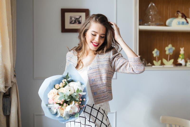 Ευτυχής γυναίκα με την ανθοδέσμη των λουλουδιών που στέκονται κοντά στο παράθυρο στοκ εικόνες
