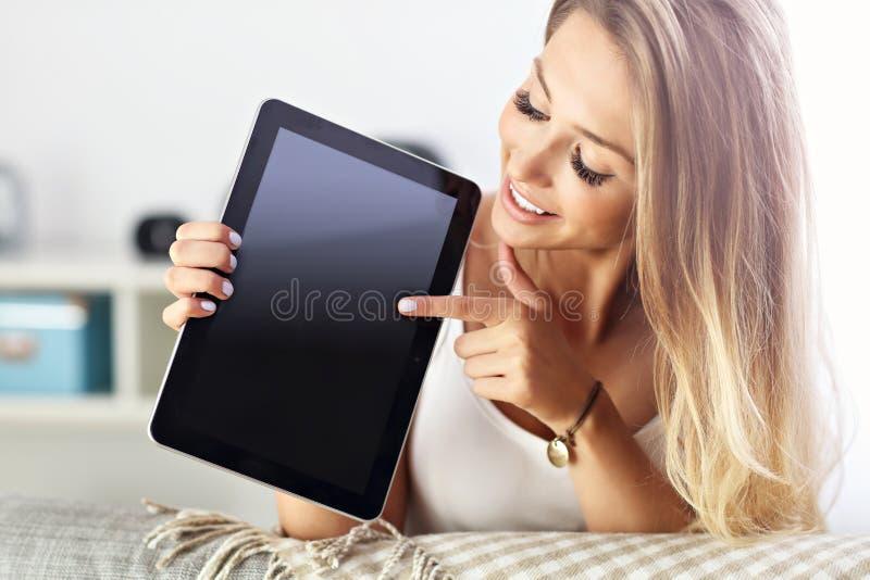 Ευτυχής γυναίκα με την ταμπλέτα στον καναπέ στοκ εικόνες