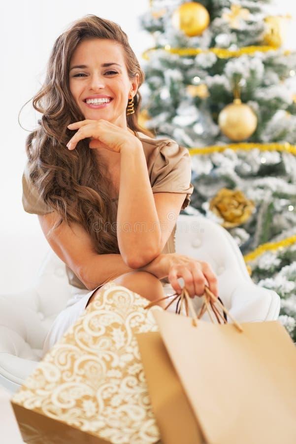 Ευτυχής γυναίκα με τις τσάντες αγορών που κάθεται κοντά στο χριστουγεννιάτικο δέντρο στοκ φωτογραφία με δικαίωμα ελεύθερης χρήσης