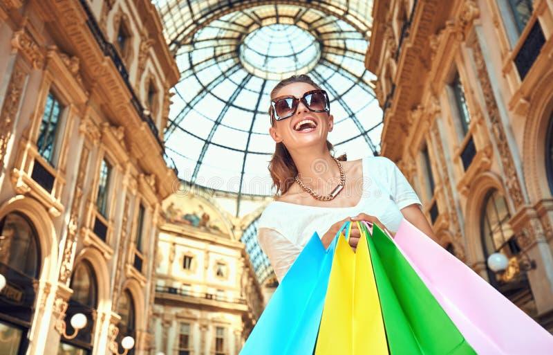 Ευτυχής γυναίκα με τις τσάντες αγορών σε Galleria Vittorio Emanuele στοκ εικόνα