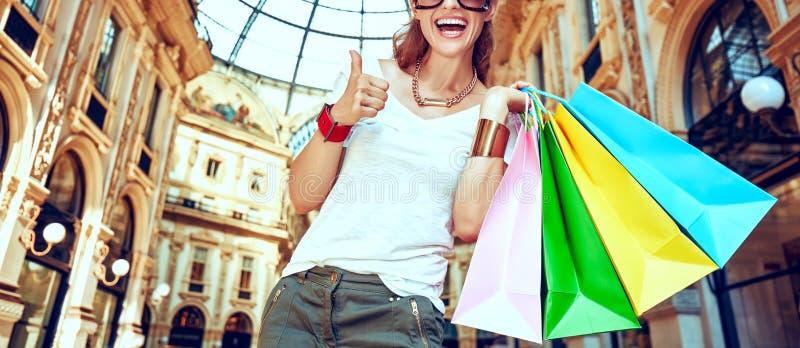 Ευτυχής γυναίκα με τις τσάντες αγορών σε Galleria Vittorio Emanuele στοκ φωτογραφία