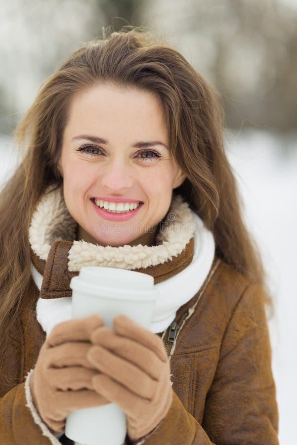 Ευτυχής γυναίκα με το καυτό ποτό το χειμώνα υπαίθρια στοκ φωτογραφία