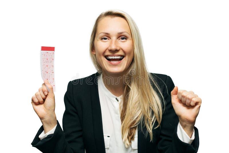 Ευτυχής γυναίκα με το τυχερό εισιτήριο λαχειοφόρων αγορών υπό εξέταση στοκ φωτογραφίες