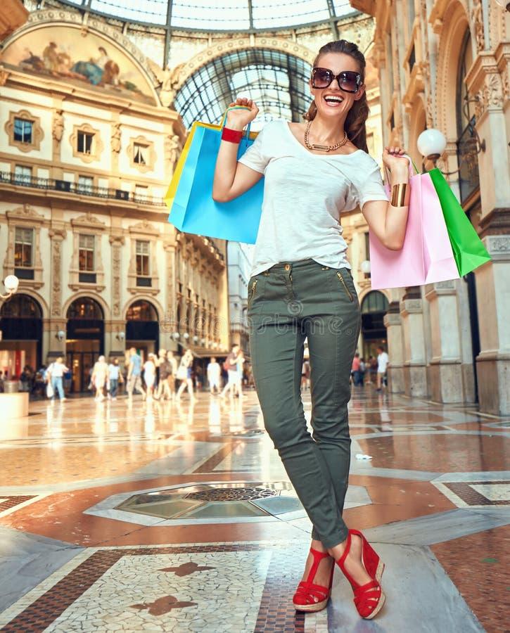 Ευτυχής γυναίκα μόδας eyeglasses με τις τσάντες αγορών σε Galleria στοκ εικόνες