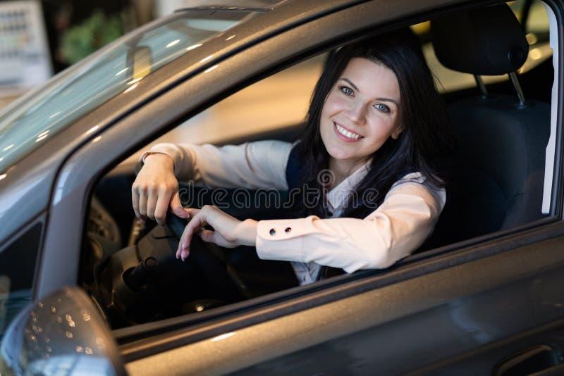 Ευτυχής γυναίκα πελατών που αγοράζει ένα νέο αυτοκίνητο στο κέντρο dealeship στοκ φωτογραφία με δικαίωμα ελεύθερης χρήσης