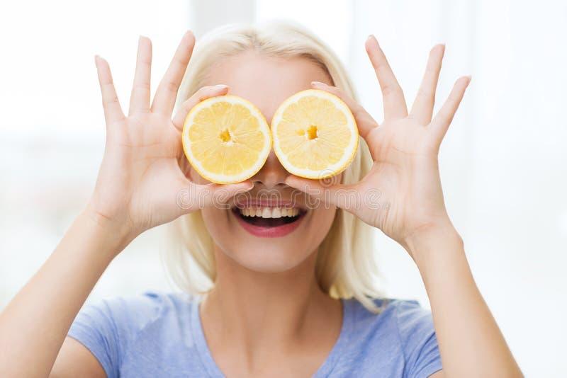 Ευτυχής γυναίκα που έχει τη διασκέδαση που καλύπτει τα μάτια με το λεμόνι στοκ εικόνες