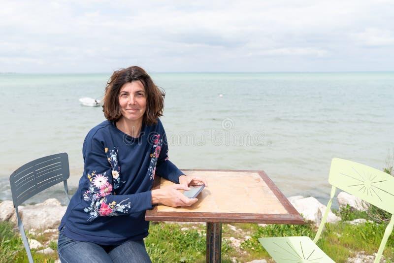 Ευτυχής γυναίκα που απολαμβάνει της ελευθερίας στον πίνακα κάτω από το υπόβαθρο παραλιών θάλασσας στις θερινές διακοπές στοκ φωτογραφία