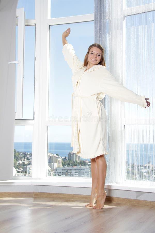 Ευτυχής γυναίκα που απολαμβάνει τη θέα θάλασσας στο ξενοδοχείο/το δωμάτιο στοκ φωτογραφία με δικαίωμα ελεύθερης χρήσης