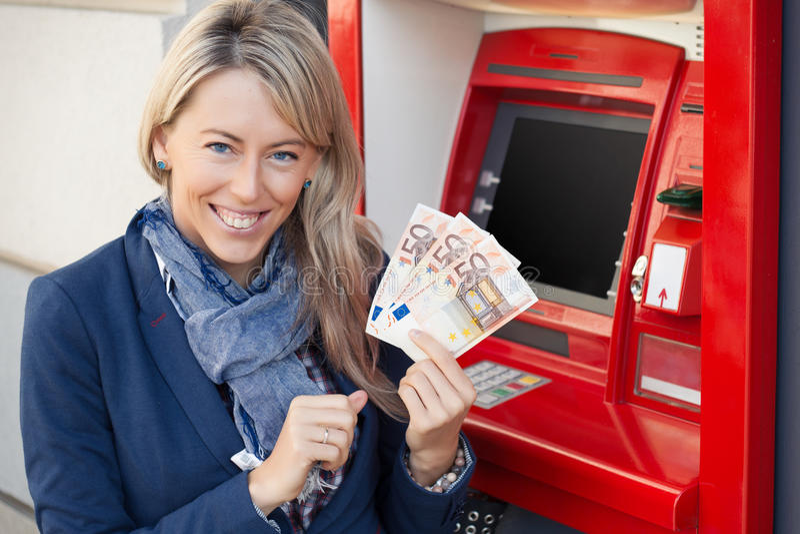 Ευτυχής γυναίκα που αποσύρει τα μετρητά από το ATM στοκ εικόνα με δικαίωμα ελεύθερης χρήσης