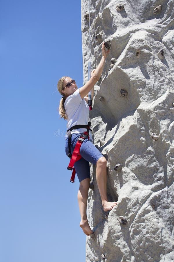 Ευτυχής γυναίκα που απολαμβάνει την αναρρίχηση βράχου ενώ στις διακοπές στοκ εικόνα με δικαίωμα ελεύθερης χρήσης