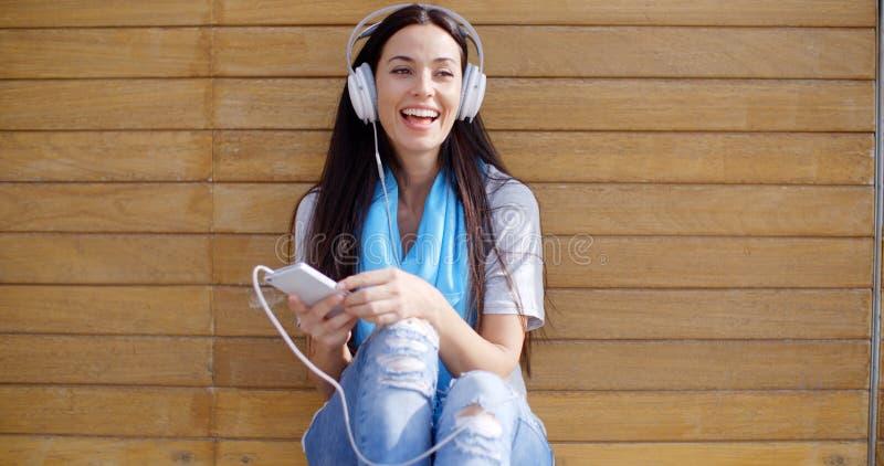 Ευτυχής γυναίκα που απολαμβάνει τη μουσική της στοκ εικόνα