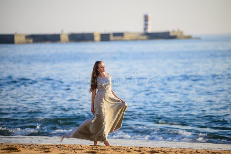 Ευτυχής γυναίκα που απολαμβάνει το ηλιοβασίλεμα στην παραλία στοκ φωτογραφία με δικαίωμα ελεύθερης χρήσης