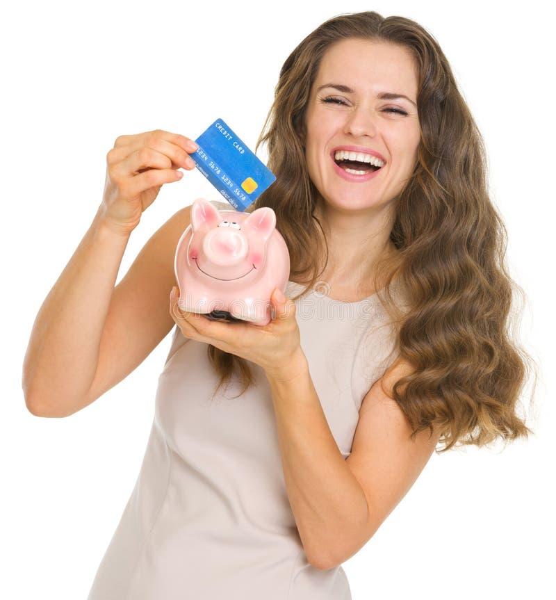 Ευτυχής γυναίκα που βάζει την πιστωτική κάρτα στη piggy τράπεζα στοκ φωτογραφία