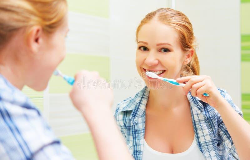 Ευτυχής γυναίκα που βουρτσίζει τα δόντια της με μια οδοντόβουρτσα στοκ εικόνες