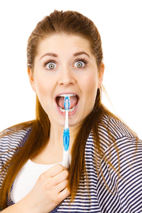 Ευτυχής γυναίκα που βουρτσίζει τα δόντια της με την οδοντόβουρτσα στοκ εικόνες
