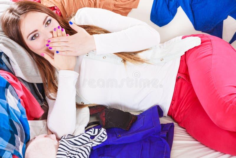 Ευτυχής γυναίκα που βρίσκεται στα ενδύματα που καλύπτουν το στόμα στοκ εικόνες
