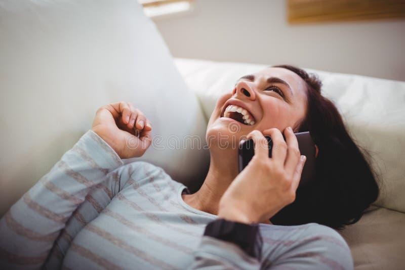 Ευτυχής γυναίκα που γελά μιλώντας στο τηλέφωνο στοκ εικόνα
