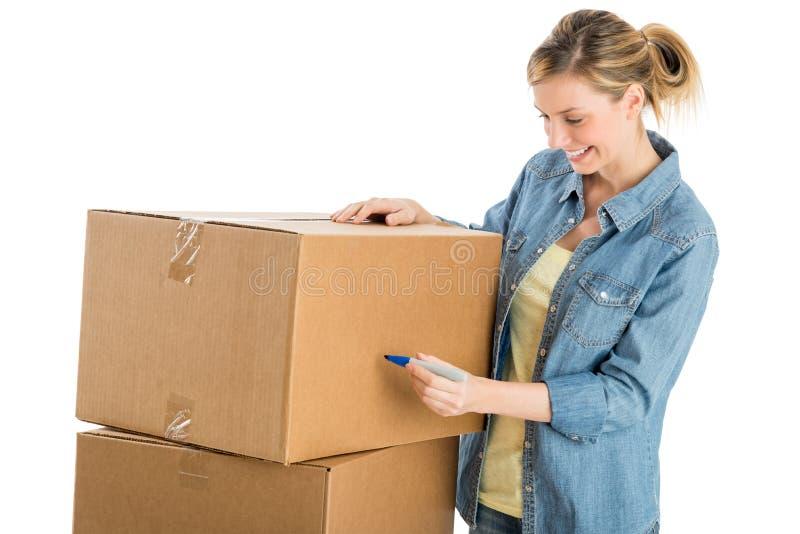 Ευτυχής γυναίκα που γράφει στα κουτιά από χαρτόνι στοκ φωτογραφίες