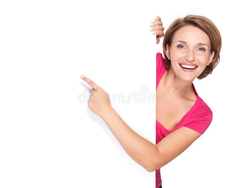 Ευτυχής γυναίκα που δείχνει με το δάχτυλό της στο έμβλημα στοκ φωτογραφίες