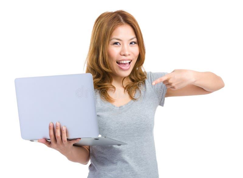 Ευτυχής γυναίκα που δείχνει το φορητό προσωπικό υπολογιστή στοκ εικόνες