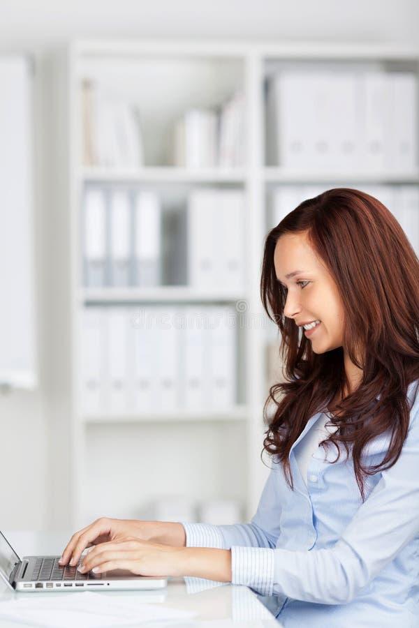 Ευτυχής γυναίκα που εργάζεται στο lap-top της στοκ φωτογραφίες