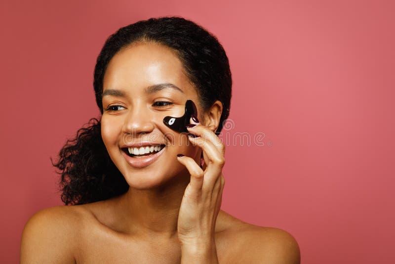 Ευτυχής γυναίκα που εφαρμόζει το μπάλωμα προσώπου με το χέρι στοκ εικόνα με δικαίωμα ελεύθερης χρήσης