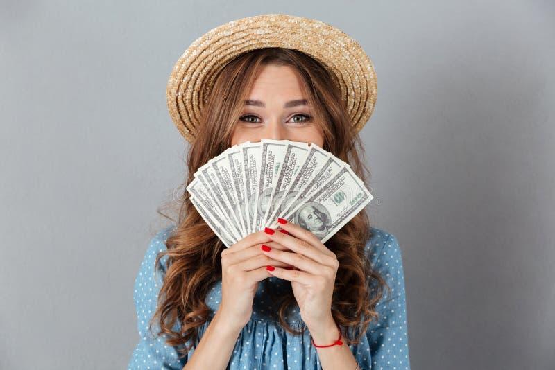 Ευτυχής γυναίκα που καλύπτει το πρόσωπο με τα χρήματα κάμερα στοκ φωτογραφία