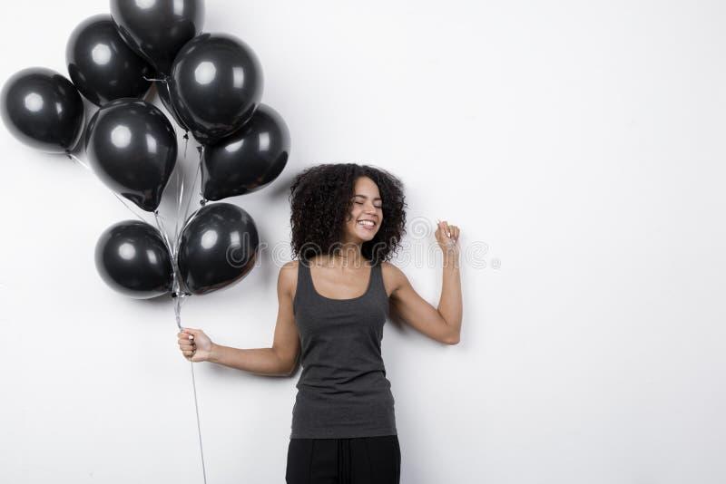 Ευτυχής γυναίκα που κρατά πολλά μαύρα μπαλόνια στοκ εικόνες