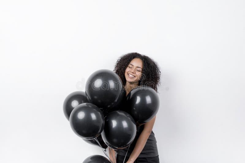 Ευτυχής γυναίκα που κρατά τα μαύρα μπαλόνια στοκ φωτογραφίες με δικαίωμα ελεύθερης χρήσης