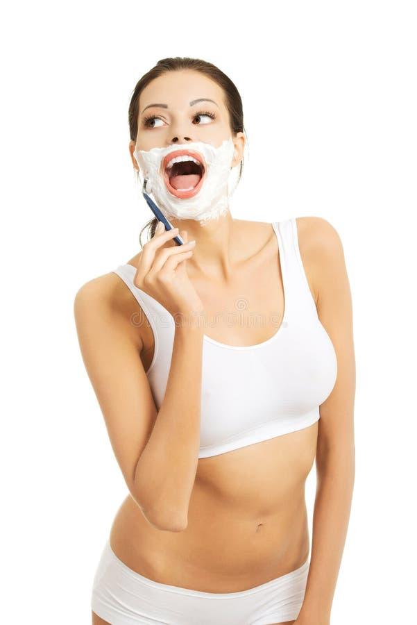 Ευτυχής γυναίκα που ξυρίζει το πρόσωπό της στοκ φωτογραφία