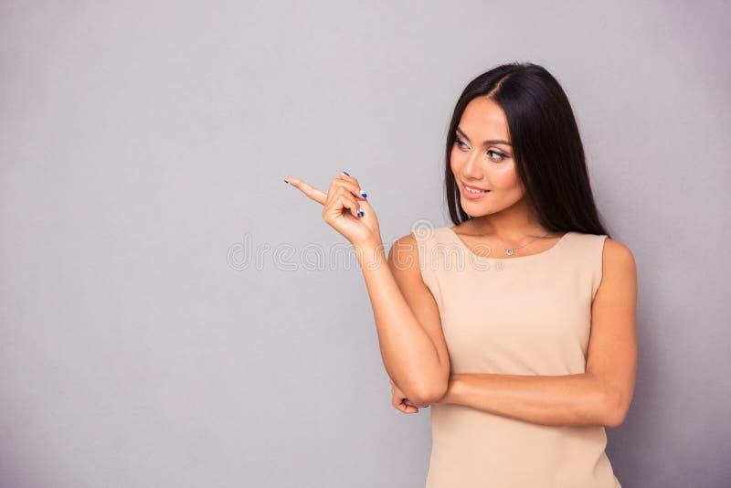 Ευτυχής γυναίκα που παρουσιάζει δάχτυλο μακριά στοκ φωτογραφία