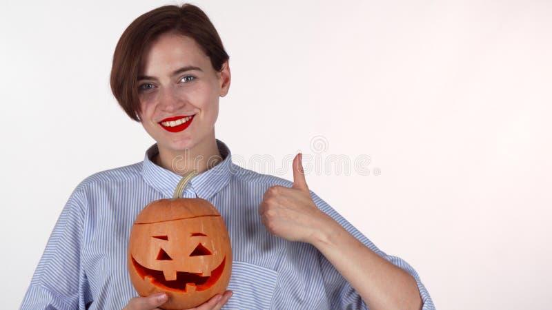 Ευτυχής γυναίκα που παρουσιάζει αντίχειρες, που κρατούν χαρασμένη την αποκριές κολοκύθα στοκ εικόνες