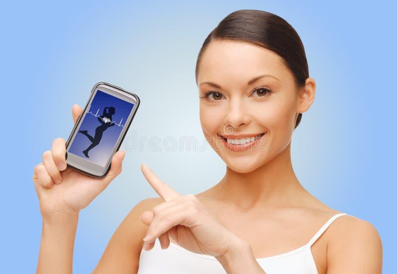 Ευτυχής γυναίκα που παρουσιάζει στο smartphone κενή οθόνη στοκ φωτογραφία