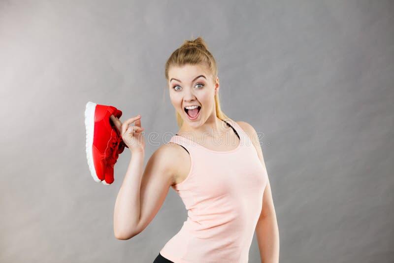 Ευτυχής γυναίκα που παρουσιάζει sportswear τα παπούτσια εκπαιδευτών στοκ φωτογραφία