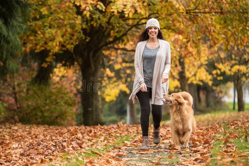 Ευτυχής γυναίκα που περπατά το χρυσό Retriever της σκυλί σε ένα πάρκο με την πτώση στοκ εικόνα με δικαίωμα ελεύθερης χρήσης
